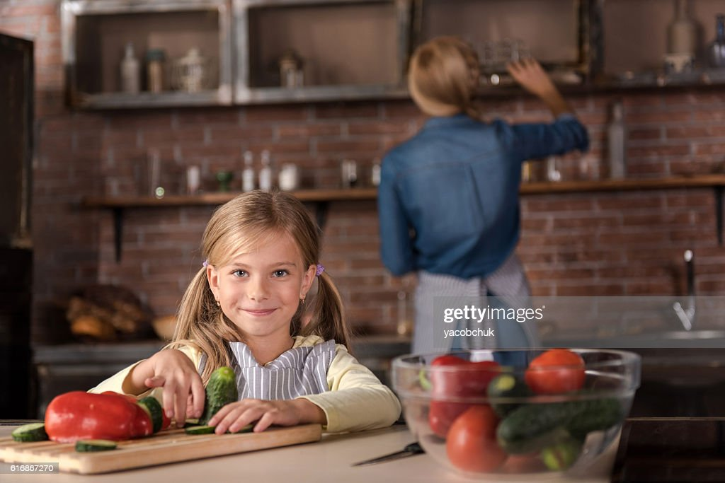 Smiling little girl touching vegetables in the kitchen : Stock Photo