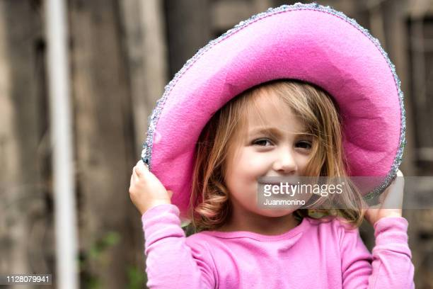 smiling little girl wearing a pink hat - brown hat stock photos and pictures
