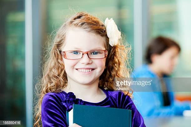 Smiling little girl with a book in the study hall