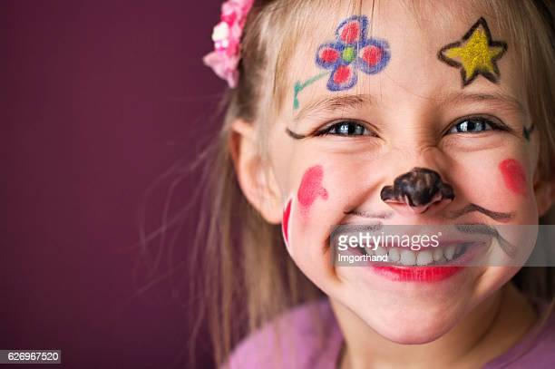 Smiling little girl with a painted face