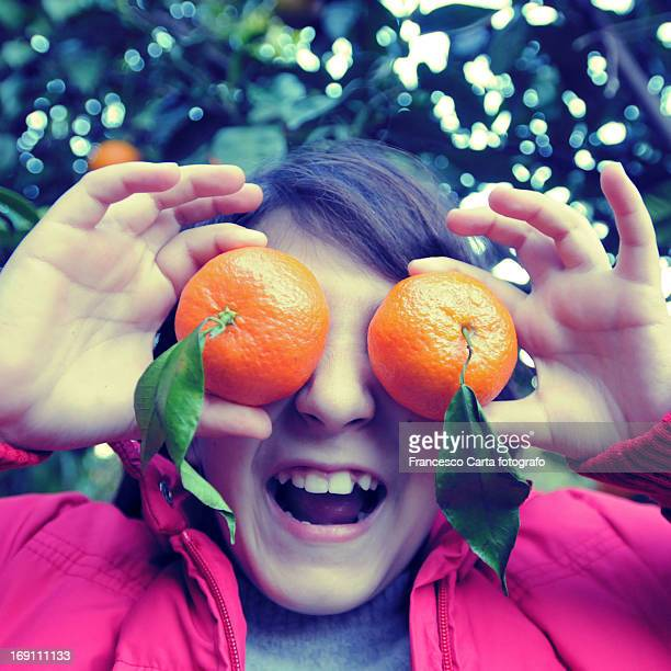 Smiling little girl with mandarins