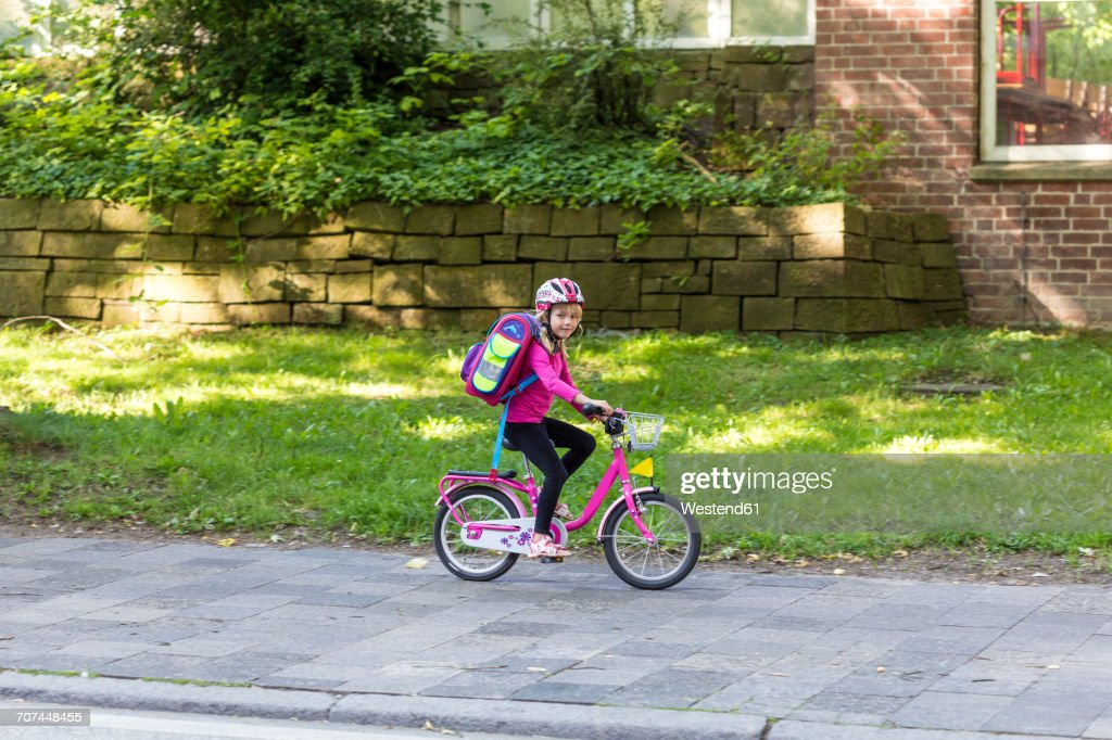 Smiling little girl with school bag riding bicycle on pavement : Stock Photo