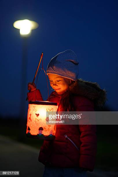 Smiling little girl with self-made paper lantern in the evening