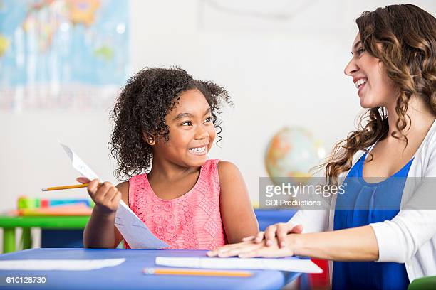 Smiling little girl working on homework with her cheerful teacher