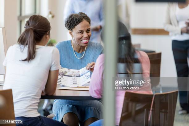 smiling loan officer talking with clients - pamphlet stock pictures, royalty-free photos & images