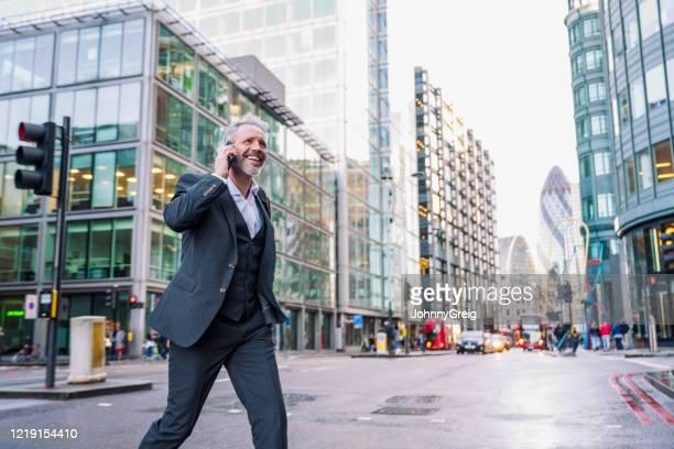 glimlachende zakenman van londen die telefoon gebruikt terwijl het kruisen van straat - zonder stropdas stockfoto's en -beelden