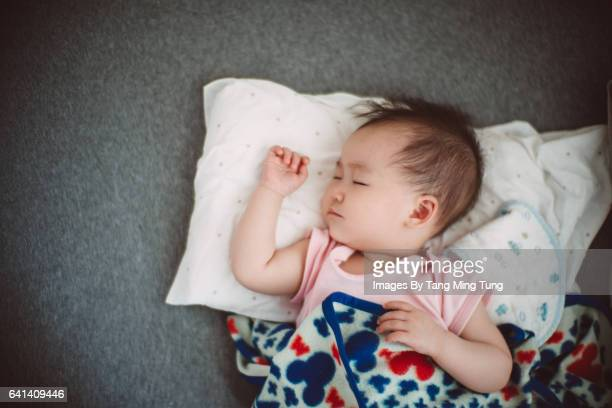 Smiling lovely baby sleeping on the bed soundly