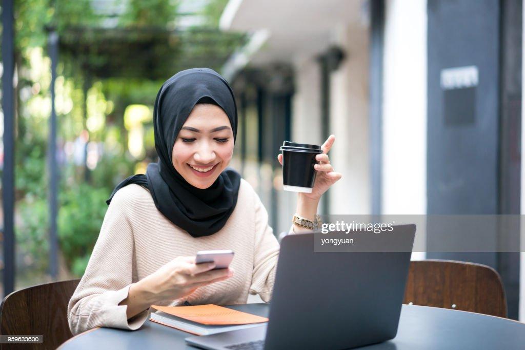 Lächelnde malaysische Mädchen mit ihrem smartphone : Stock-Foto