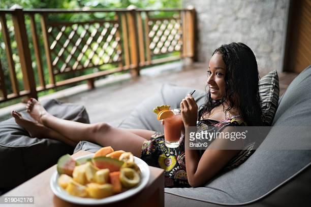 マレーシアの笑顔の女性にカクテルを楽しみながらテラスでます。