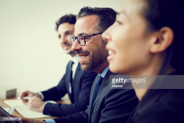 smiling male and female financial colleagues sitting in office during meeting - lawyer stock pictures, royalty-free photos & images
