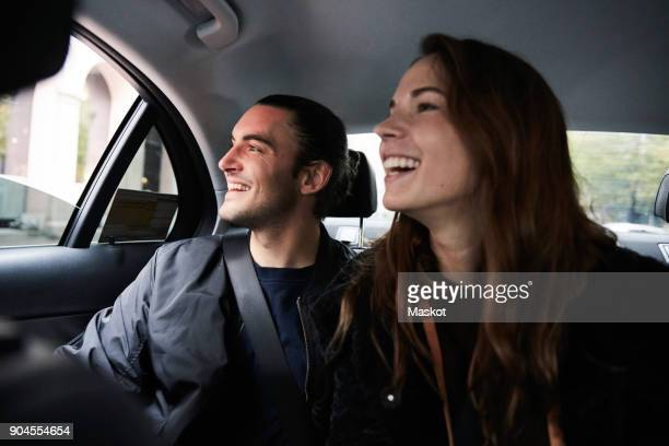 smiling male and female friends looking through window while riding in car - friends inside car stock photos and pictures