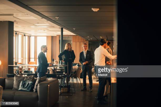 smiling male and female professionals at coffee break in law office - public building stock pictures, royalty-free photos & images