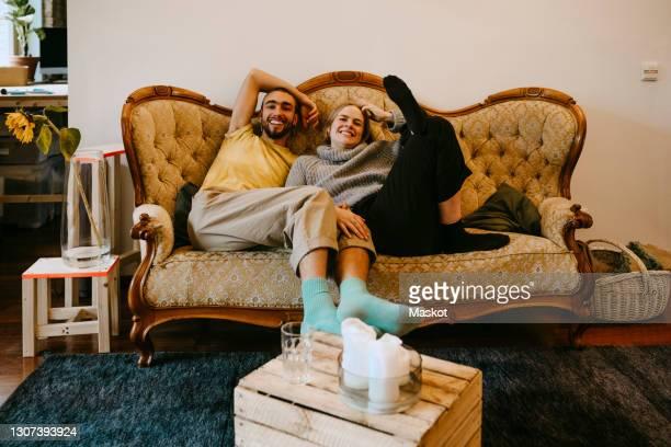 smiling male and female roommates sitting on sofa at home - 30 34 anos imagens e fotografias de stock