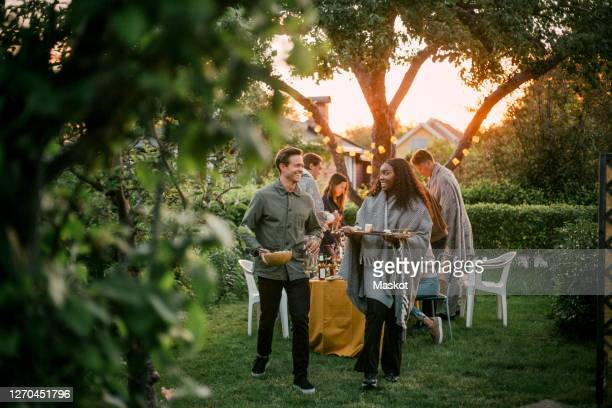 smiling male and female talking in yard during dinner party - garden party stock pictures, royalty-free photos & images
