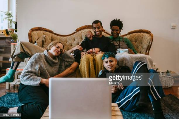 smiling male and female watching movie on laptop in living room - roommate stock pictures, royalty-free photos & images