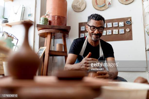 smiling male artist making pottery in workshop - pottery stock pictures, royalty-free photos & images