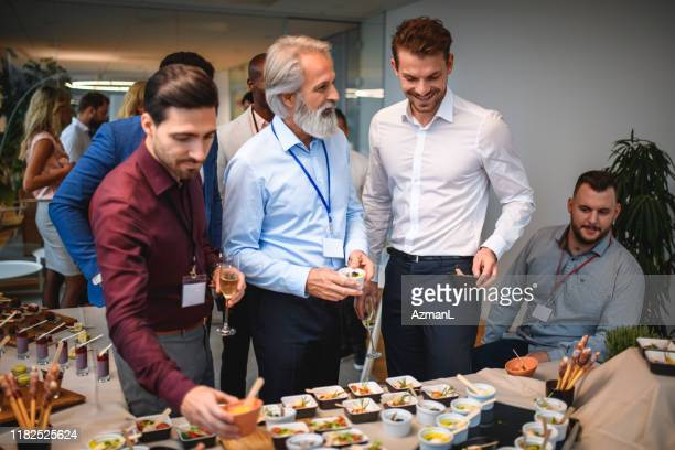 smiling male associates deciding over gourmet appetizers - launch event stock pictures, royalty-free photos & images