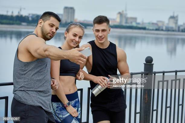 Smiling male athlete taking selfie with friends while standing against lake