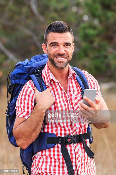 Smiling male backpacker using smart phone in mountain
