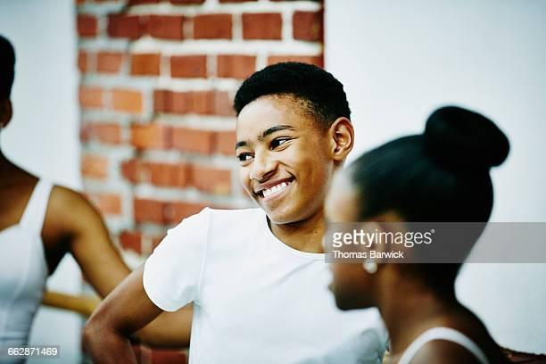 Smiling male ballet dancer with classmates