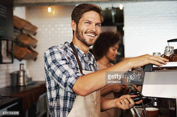 Smiling male barista preparing coffee