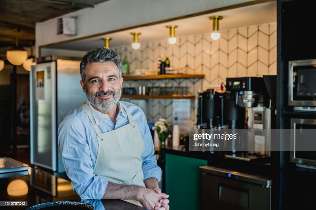 Glimlachende mannelijke barista klaar om drank in koffiestaaf te bereiden : Stockfoto