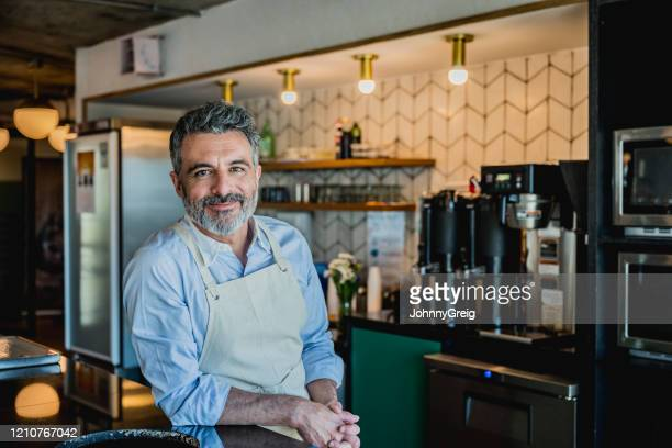 smiling male barista ready to prepare drink in coffee bar - business owner stock pictures, royalty-free photos & images
