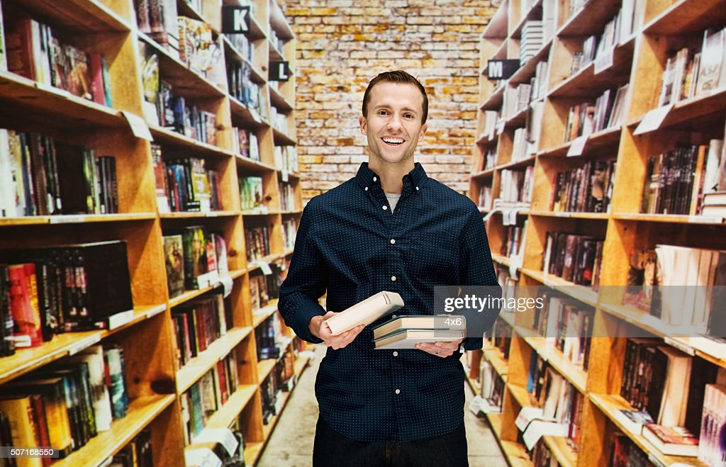Smiling male bookseller in library : Stock Photo