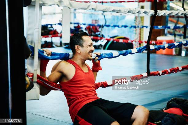 smiling male boxer sitting against ropes of boxing ring while resting during workout - boxing shorts stock pictures, royalty-free photos & images
