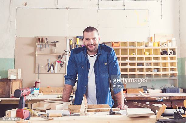 Smiling male carpenter in a construction workshop