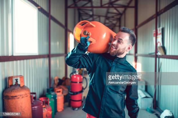 肩にガスボンベを運ぶ笑顔の男性 - キャニスター ストックフォトと画像