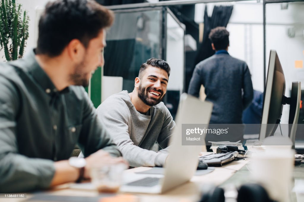 Smiling male colleagues looking at each other while sitting by desk in office : ストックフォト