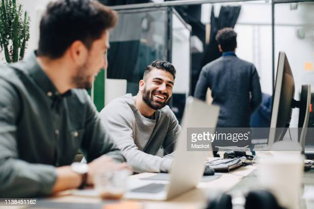 smiling male colleagues looking at each other while sitting by desk in office - deskundigheid stockfoto's en -beelden