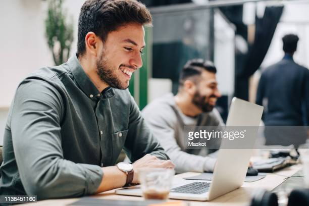 smiling male colleagues working at desk in office - smart casual stock pictures, royalty-free photos & images