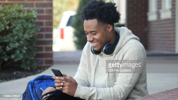 smiling male college student using smartphone - college application stock photos and pictures