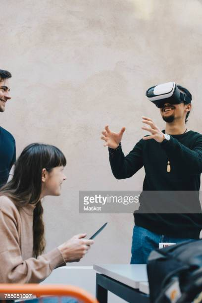 Smiling male computer programmer gesturing while using VR glasses by colleagues in office
