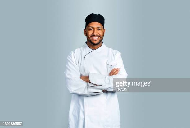 smiling male cook on gray background - chef stock pictures, royalty-free photos & images