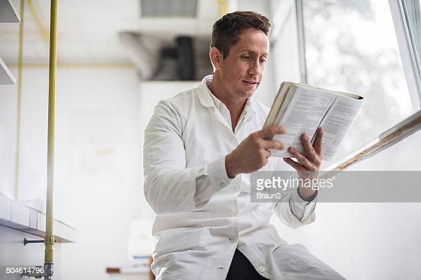 Smiling male doctor analyzing a medical book in laboratory.