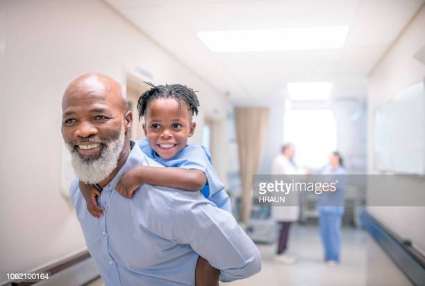 Smiling male doctor giving piggyback to patient