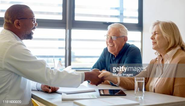 smiling male doctor shaking hand with senior woman - trust stock pictures, royalty-free photos & images