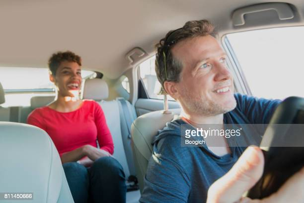 smiling male driver gives ride to smiling passenger in backseat - driver stock photos and pictures