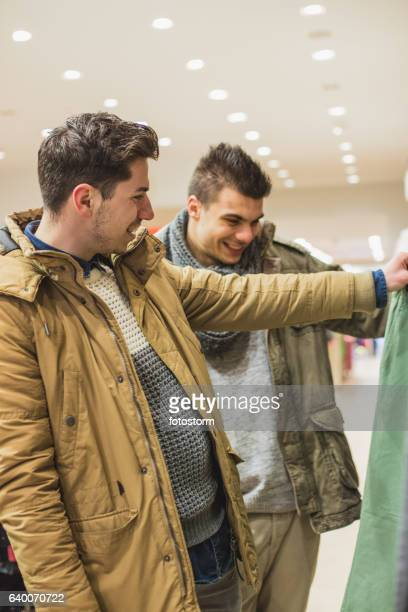 Smiling male friends in boutique