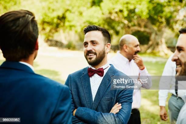 smiling male friends in discussion during outdoor wedding reception - festlich gekleidet stock-fotos und bilder