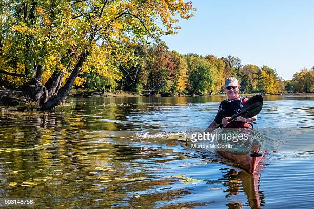 Smiling male kayaker paddling in front of beautiful fall foliage
