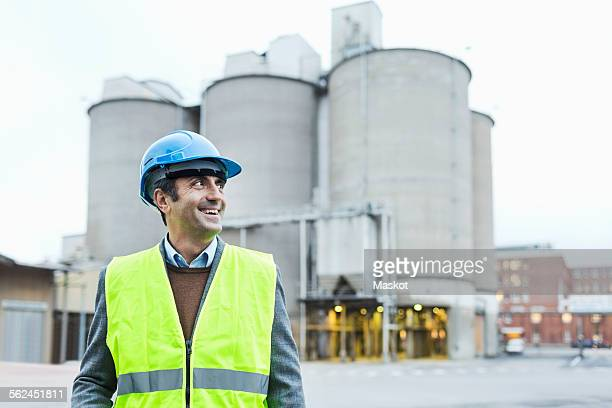 Smiling male manual worker looking away while standing against cement silos