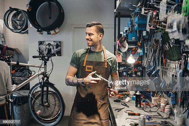 Smiling male mechanic looking at colleague while repairing pedal in workshop
