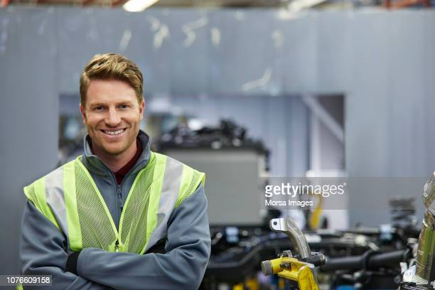 smiling male mechanical engineer with arms crossed - mechanical engineering stock pictures, royalty-free photos & images