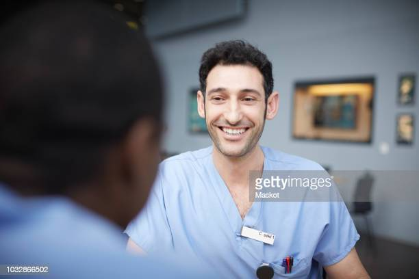 smiling male nurse talking with coworker at cafeteria in hospital - infirmier photos et images de collection