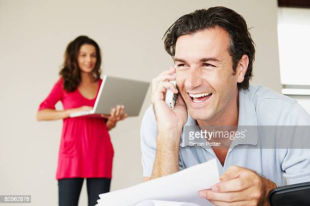 Smiling male on phone with bills