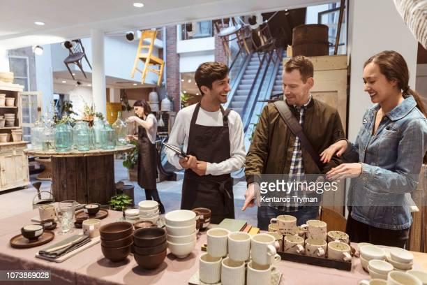 smiling male owner discussing over merchandise with couple at boutique - utensílio de cozinha equipamento doméstico - fotografias e filmes do acervo